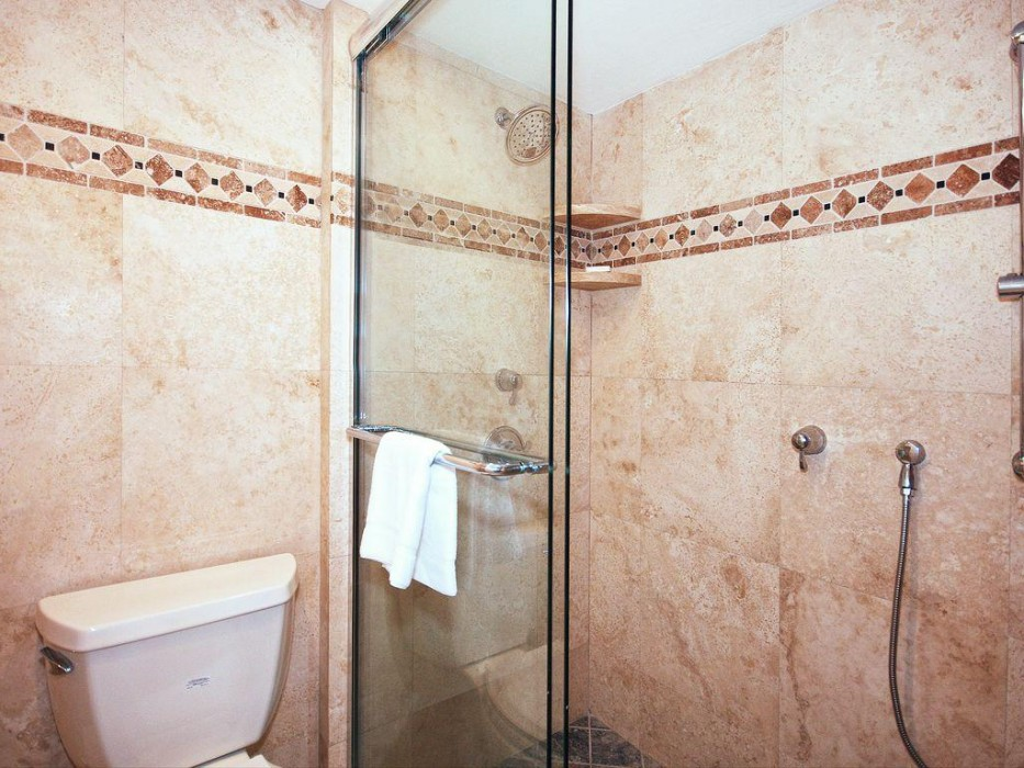 Extra long shower with bench seat, wall rain shower head and separate shower wand.
