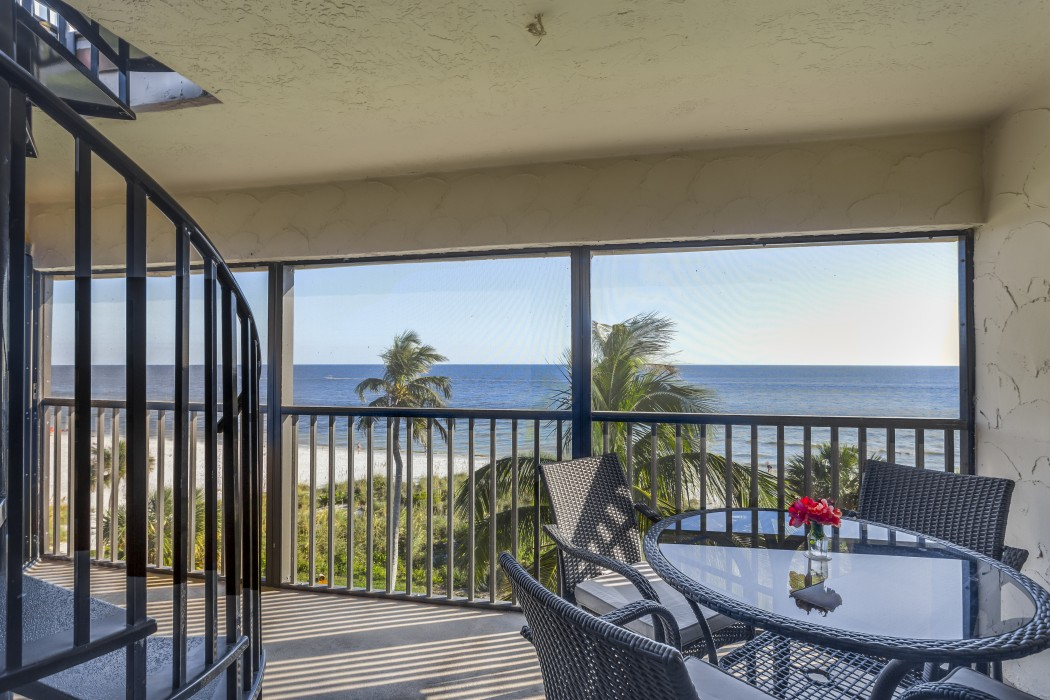 Private screened lanai accessible via the master suite or living room with direct beachfront views.