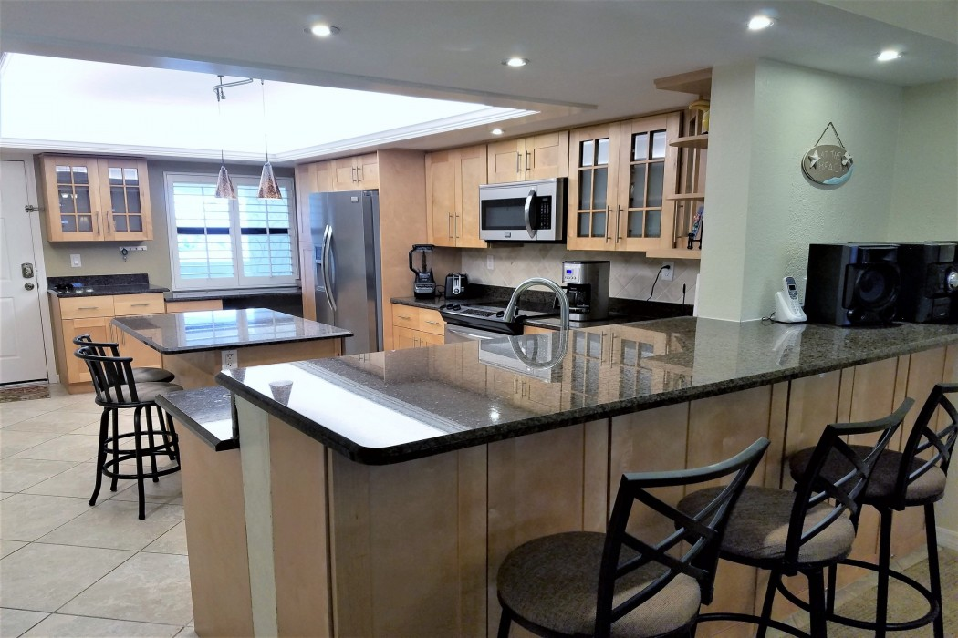 The large, fully equipped kitchen has stainless appliances and granite counters.