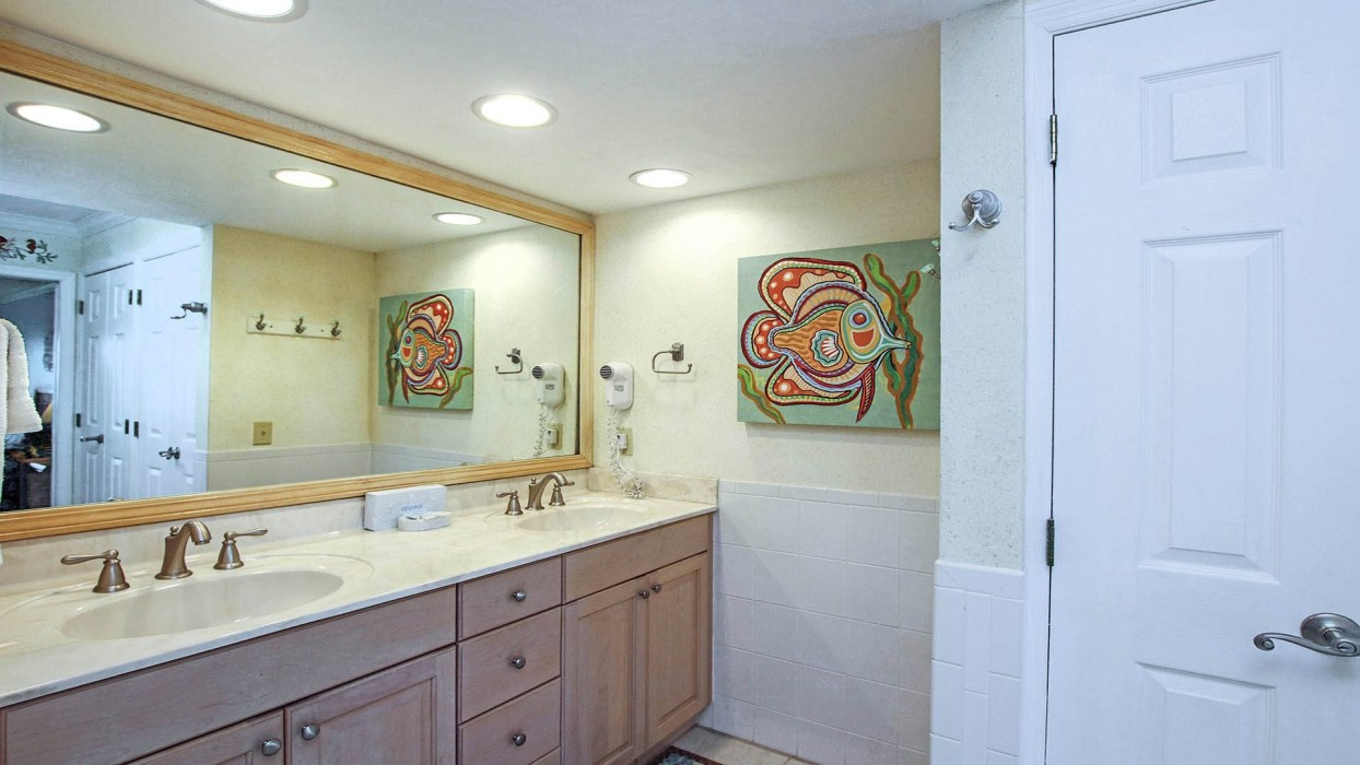 The master bathroom has double sinks and a marble-tiled shower.  The sink cabinet was recently painted a soft sage green and has a new quartz countertop and new sinks; new photos of the updates will be added soon.